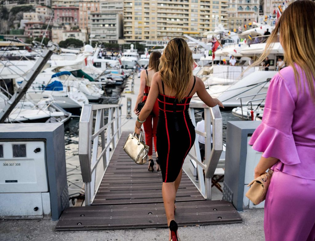 Women walking towards luxury yachts at the Monaco harbour. - AFP
